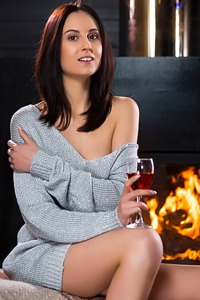 Sade Mare sits drinking wine wearing a grey wool dress